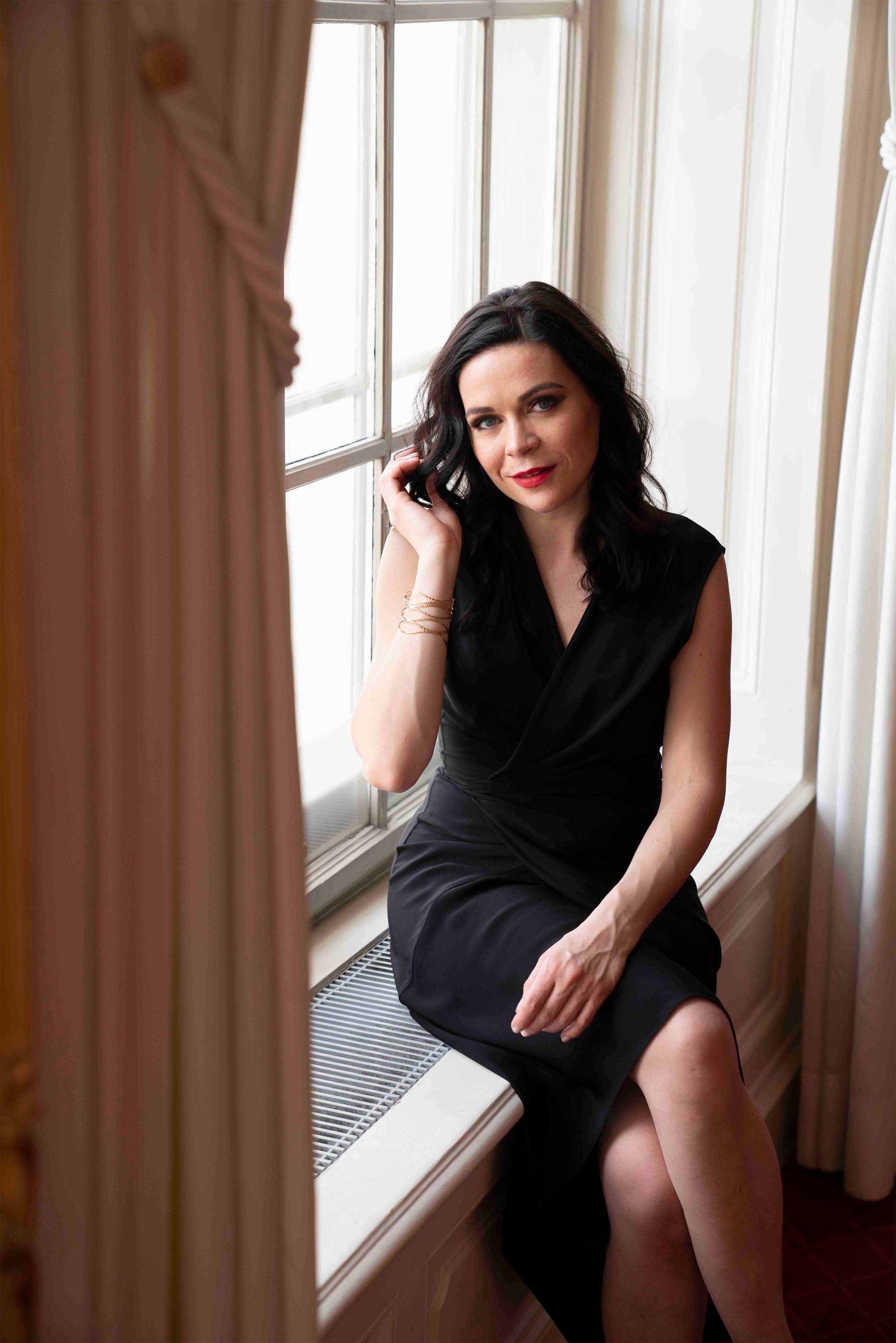 Sieglinde Feldhofer sitzt auf einer Fensterbank in der Grazer Oper während sie in die Kamera lächelt © Sara Sera