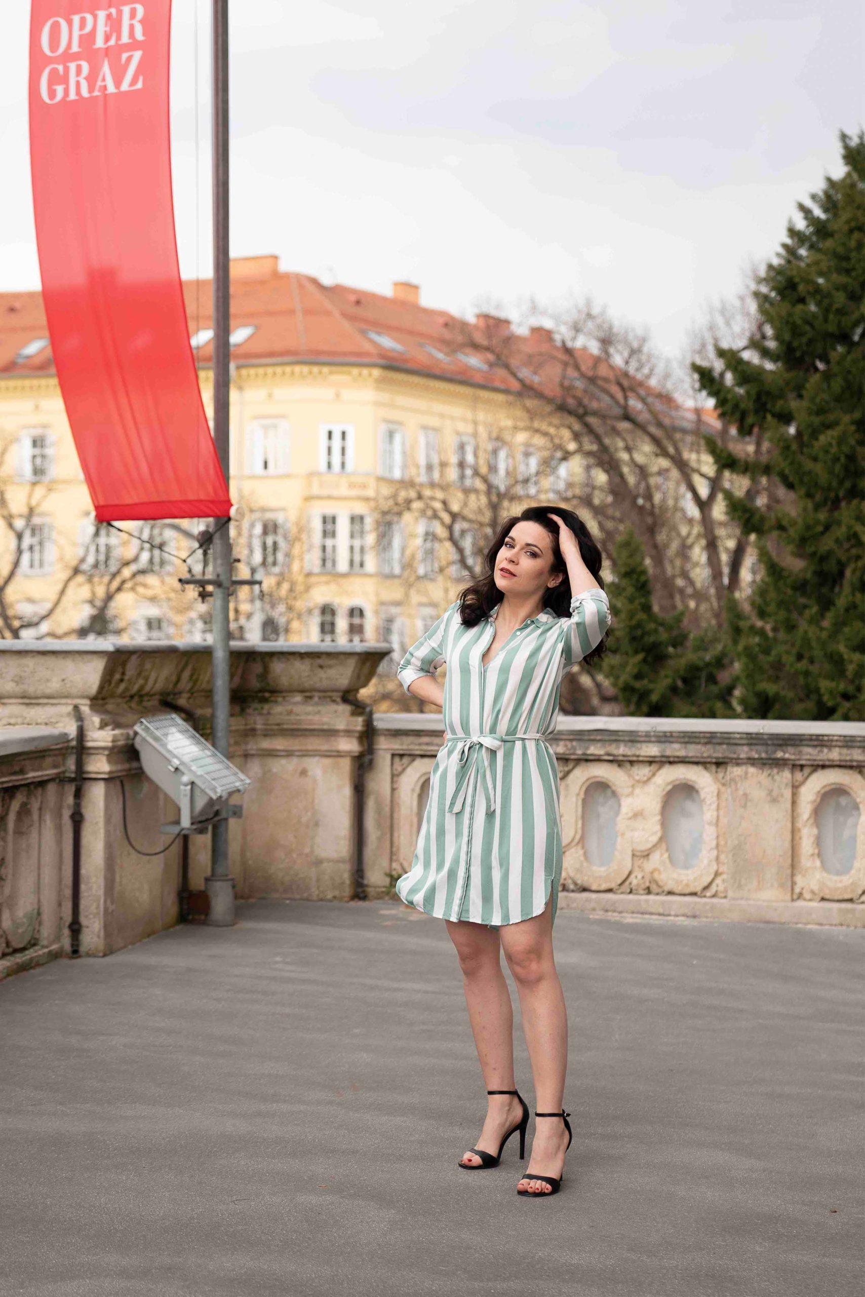 Sieglinde Feldhofer in grün gestreiftem Kleid auf dem Balkon der Grazer Oper © Sara Sera