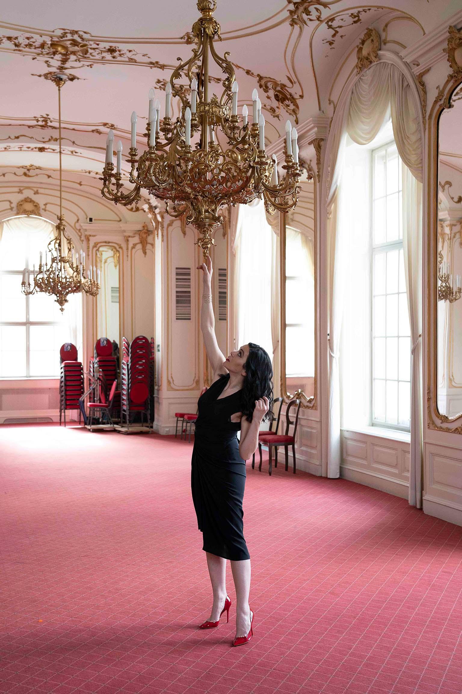 Sieglinde Feldhofer bei Fotoshooting unter einem prunkvollem Kronleuchter in der Grazer Oper © Sara Sera